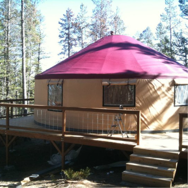 tan shelter designs yurt with a red roof