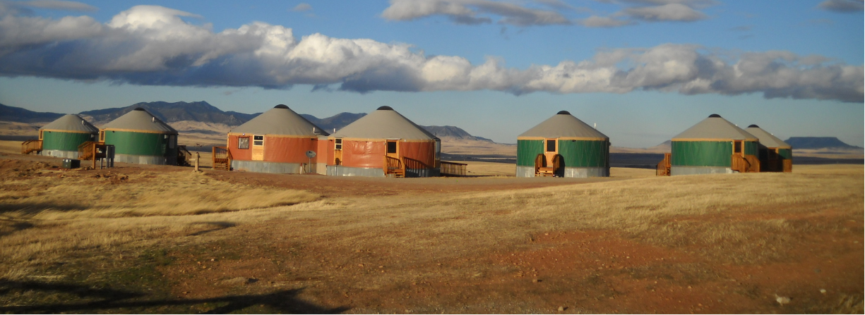 5 green and 2 orange yurts in montana