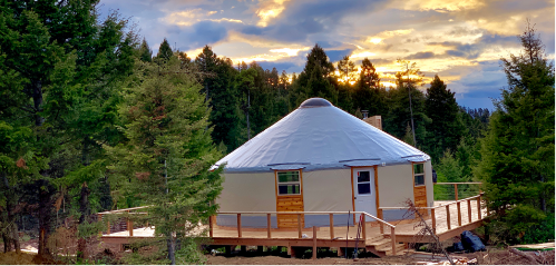 tan yurt with a grey roof on a large deck in the trees