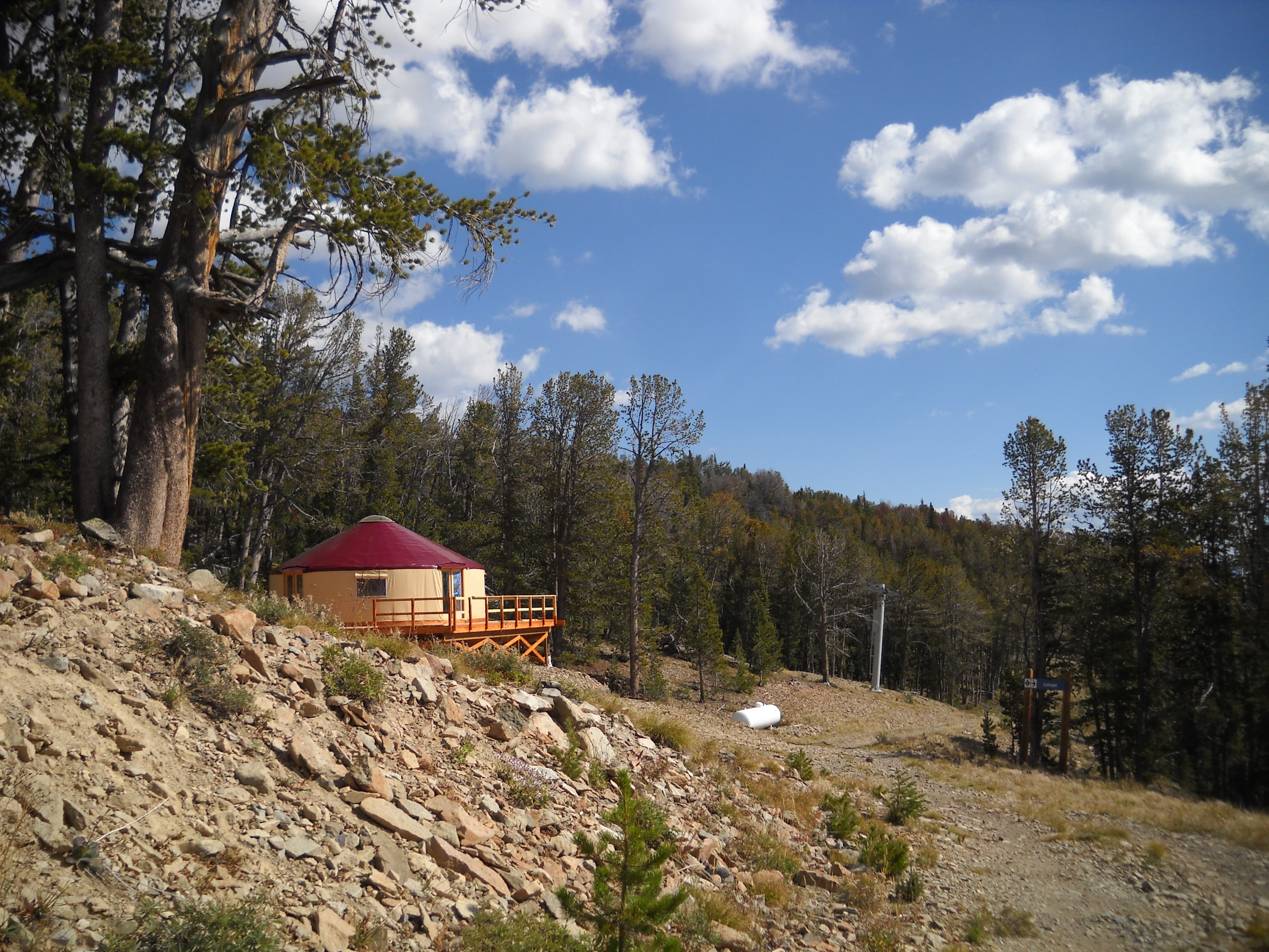 tan yurt with a red roof in the montana forest