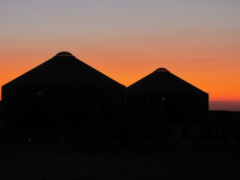 two shelter designs yurts with a sunset