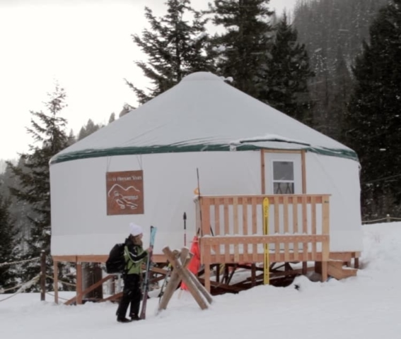person with skis in front of a yurt ski lodge