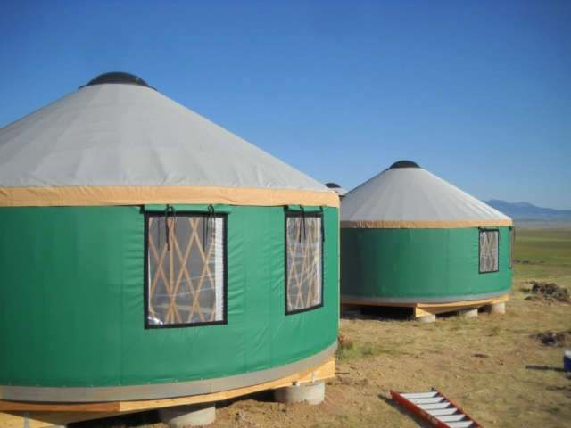 two green yurts with grey roofs
