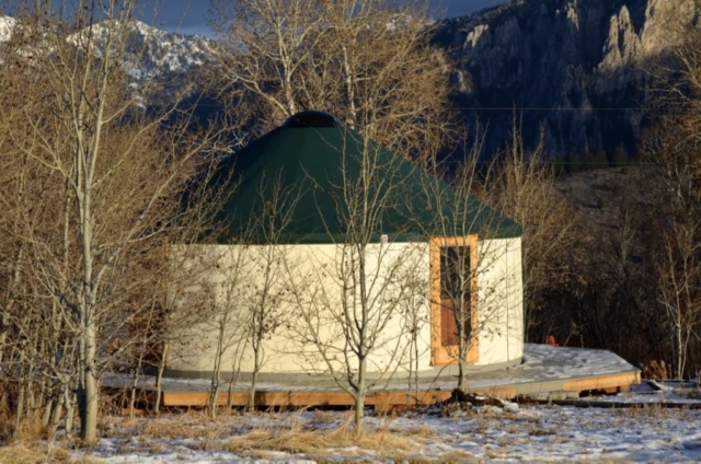 white yurt with a green roof